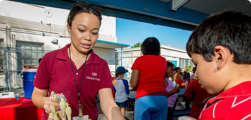 Cedars-Sinai Community Benefit employee at an elementary school, helping kids with Healthy Habits.