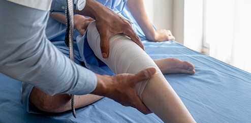 Stock image of physical therapist working on a patient knee.