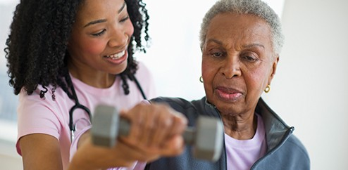 Stock image of physical therapist working with male patient to rehab his shoulder.