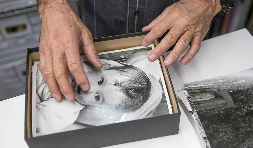 Leigh Wiener's son Devik examines the images in his father's archives, including this photo of himself as a baby.