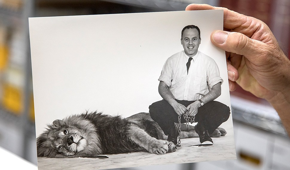 Devik Wiener holds a photo of his father photojournalist Leigh Wiener in his heyday with a tame lion.