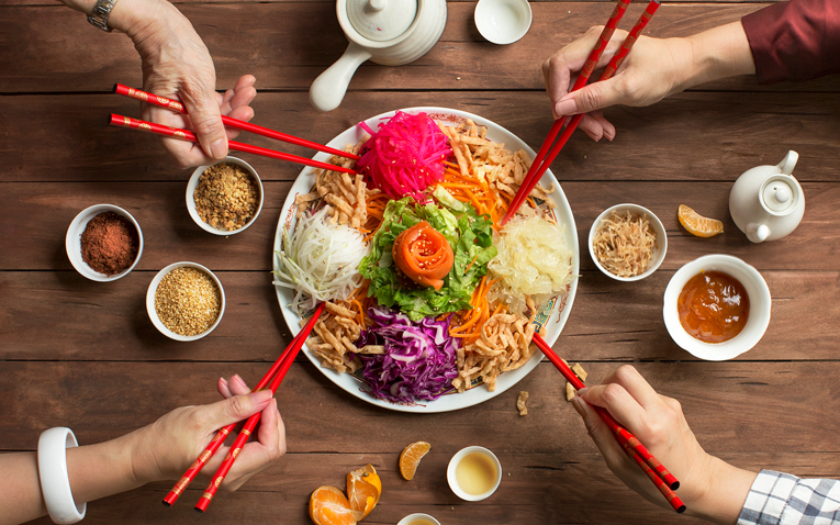 Four people holding chopsticks share a plate of food.