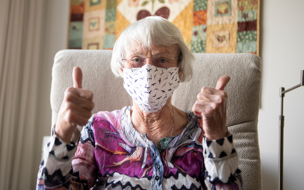 An older adult woman with a mask on to avoid COVID-19 giving the thumbs up after getting help from friends and family.