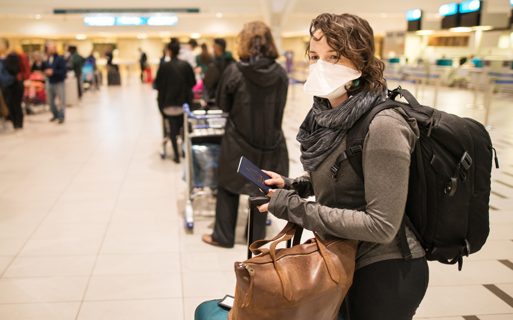 A young woman with a mask in an airport traveling during the COVID-19 pandemic.