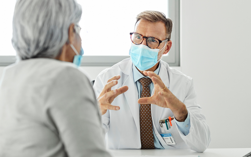 A doctor talking to a patient in office during the COVID-19 pandemic.
