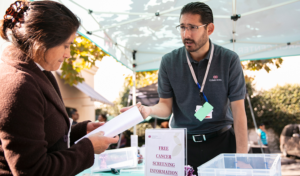 Ergueen Herrera, community outreach coordinator at the Research Center for Health Equity, setting up an information booth at the St. Thomas the Apostle church to provide navigation to free local cancer screening resources in the Pico/Union neighborhood of Los Angeles. (2018)