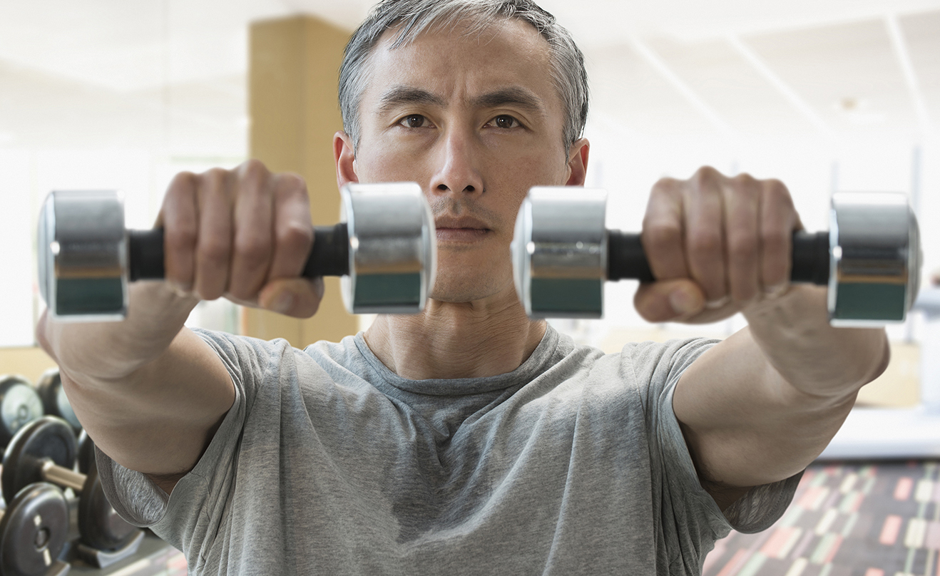 Chinese man lifting weights in gym