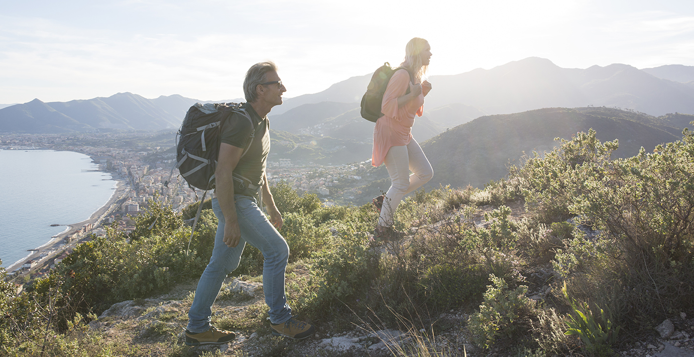 Hikers climb Mediterranean hillside, above sea