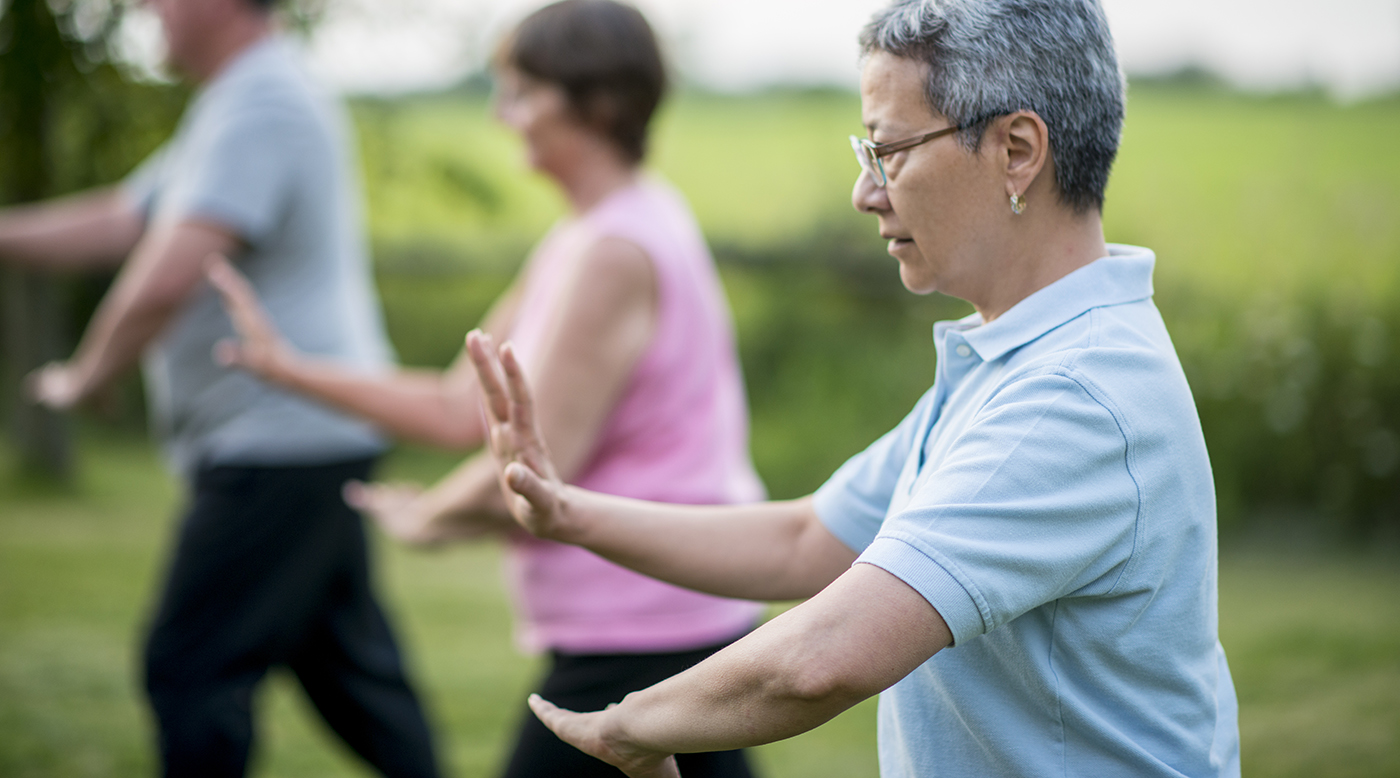 A multi-ethnic group of adult men and women are outdoors in a public park. They are wearing casual clothing while at a Tai Chi class. An Asian woman is in focus.