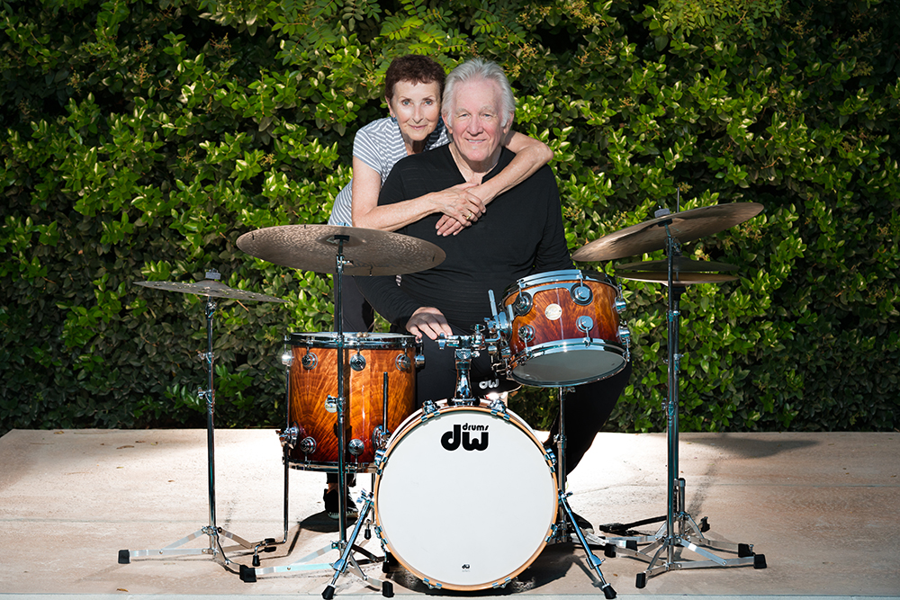 Denny Seiwell sitting behind his drum kit with wife Monique