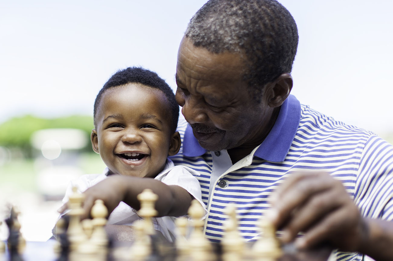 African American grandfather playing chess with smiling grandson.