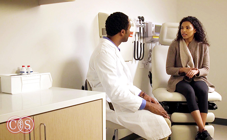 Doctor talking to a sitting woman patient