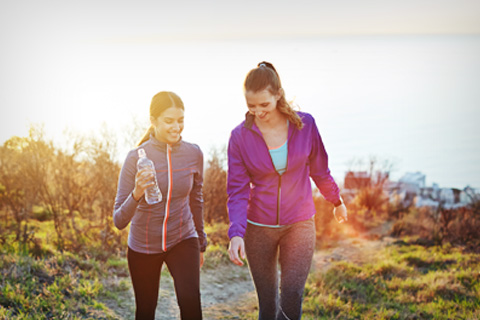 Two women hiking (holding water bottle)